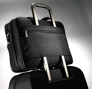 The Samsonite Classic Two Gusset Toploader can fit over the telescopic handle of a rolling briefcase.